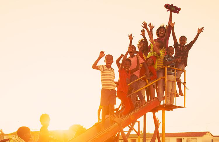 School children and teacher waving at an Ubuntu centre