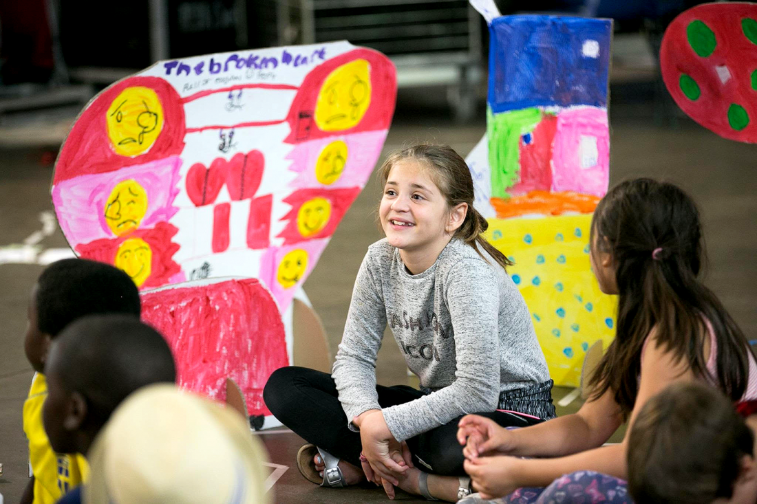 A young girl smiling, participating in a Futureheads creative workshop