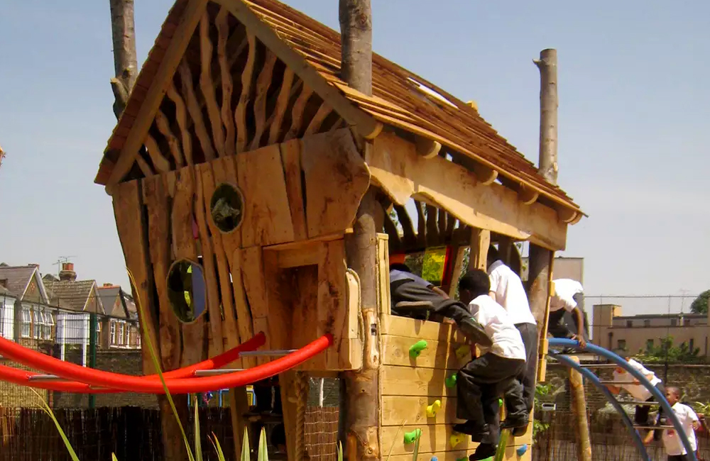 Children playing in a Made From Scratch adventure playground building